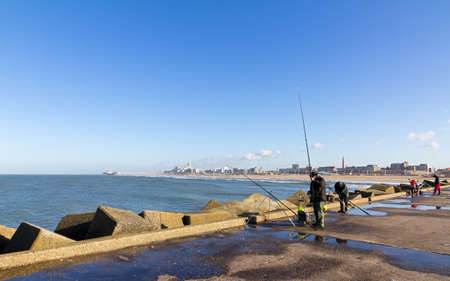 Fishermen on a jetty in Scheveningen, The Netherlands, with Scheveningen in the background photo