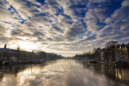 Beautiful winter panorama of the river Amstel in Amsterdam, the Netherlands, looking towards the skinny bridge