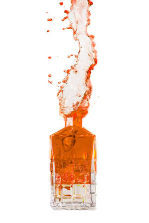 Crystal bottle with liquid splashing out on a white background photo