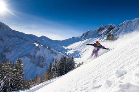 Awesome snowboarder is having fun in the backcountry powder of Les Portes du Soleil in France 스톡 콘텐츠