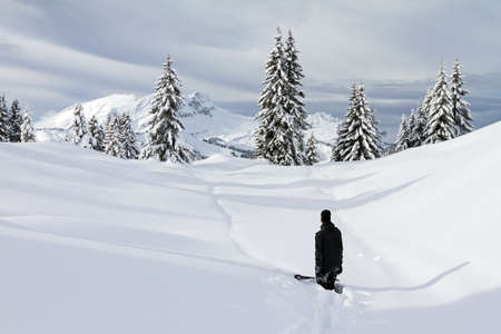 off piste: Snowboarder hiking up the mountain in the fresh powder in the backcountry of Les Portes du Soleil