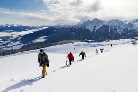 thrill: Group of skiers and snowboarders hiking to the top of a mountain