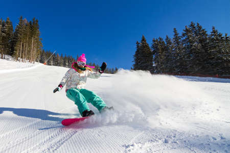 Female snowboarder on the slopes on a sunny morning in the Italian alps photo