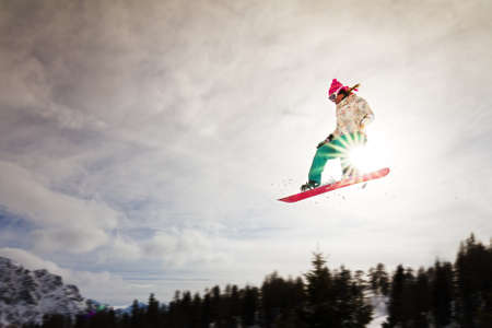 Female snowboarder making an awesome big jump of a kicker