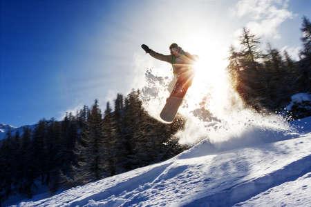 バックカントリー パウダーでキッカーを飛び越えてスノーボーダーの強力なイメージ 写真素材