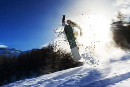 Powerful image of a snowboarder jumping over a kicker in the backcountry powder Stock Photo