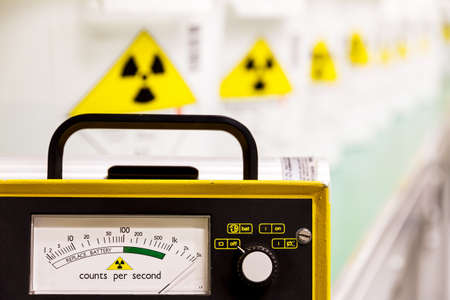 Geiger counter with radioactive materials in the background photo