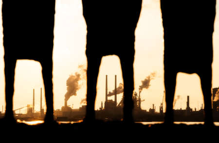 Look, through the  legs  of a statue in IJmuiden, at the heavy industry at sunset in the Netherlands photo