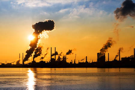 sea pollution: Sunset view of the heavy industry with smoking chimneys in IJmuiden, the Netherlands Stock Photo
