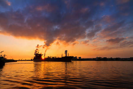 ijmuiden: Silhouette of a big cargo ship and industry at sunset in IJmuiden in the Netherlands Stock Photo