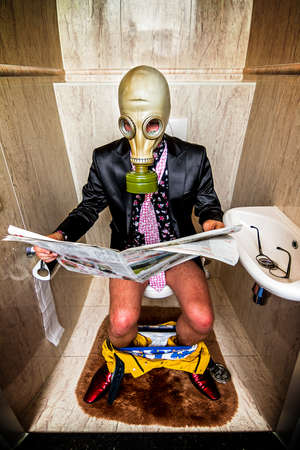 paper mask: Man reading a newspaper on the toilet wearing a gasmask to protect him against smelly bussiness Stock Photo