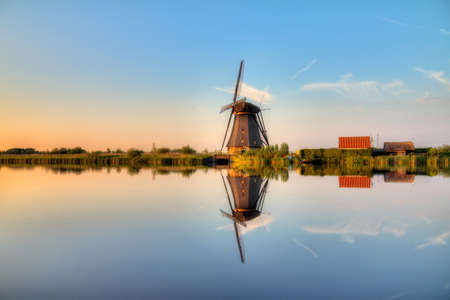 Beautiful image of a dutch windmill at sunset at Kinderdijk in the Netherlands  photo