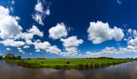 Typical dutch river landscape in spring at the river with a beautiful cloudscape in Baambrugge, the Netherlands  photo