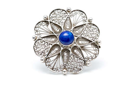 brooch: Handcrafted antique brooch in the shape of a flower with a blue stone  lapis lazuli  in the middle Stock Photo