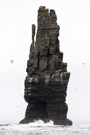Large rock rising out of the sea at the cliffs of Moher in Ireland photo