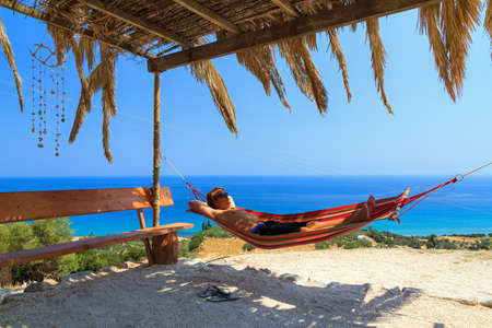 Young man relaxing in a hammock on the island of Zakynthos, Greece photo