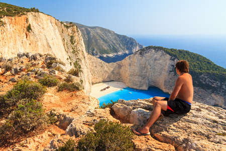 Young man looks down on Shipwreck beach on top of the high cliffs on the island of Zakynthos in the afternoon photo