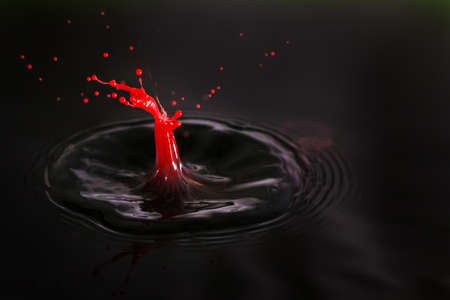 Beautiful image of a drop of red cream falling into dark water in the shape of a little man getting shot photo