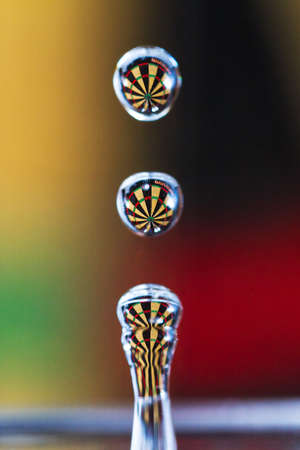 Beautiful macro image of a dartboard in the background refracted in a drop of water photo