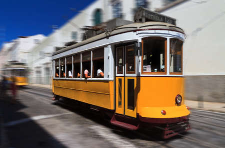 Beautiful traditional yellow tram in the streets of Lisbon, Portugal, in summer