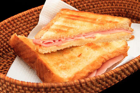 Grilled ham and cheese sandwich in a basket on a black background
