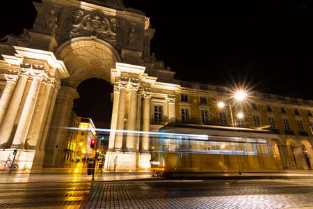Moving yellow tram in front of the gate at the commerce square at night in Lisbon, Portugal photo