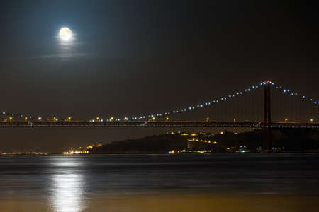 25 de Abril bridge at night with a full moon in Lisbon, Portugal photo