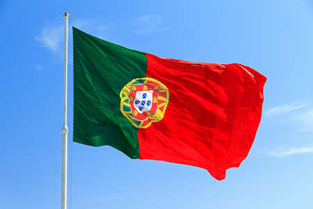 Beautiful large Portuguese flag waving in the wind against a blue background in Lisbon, Portugal photo