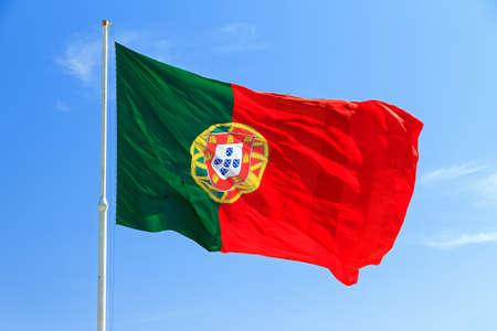 bandera de portugal: Hermosa gran bandera portuguesa ondeando en el viento contra un fondo azul en Lisboa, Portugal