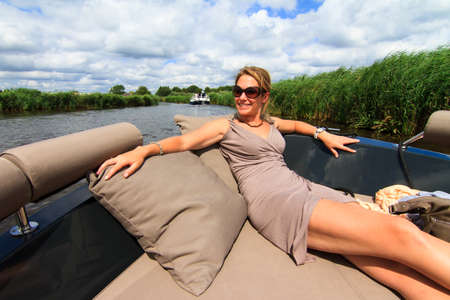 motor yacht: Beautiful lady sitting in front on a barge on a sunny summer day in the Netherlands Stock Photo