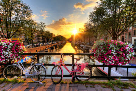 canals: Beautiful sunrise over Amsterdam, The Netherlands, with flowers and bicycles on the bridge in spring