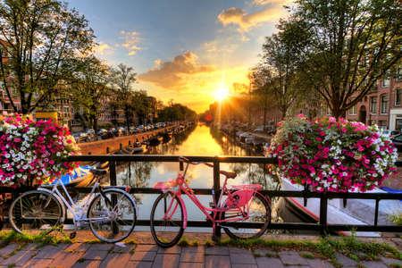 Prachtige zonsopgang boven Amsterdam, Nederland, met bloemen en fietsen op de brug in het voorjaar