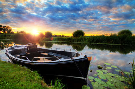 Modern and luxurious synthetic motor sloop in a river in the Netherlands at sunset
