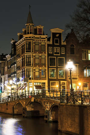 Moody night shot at the canals in Amsterdam, the Netherlands photo