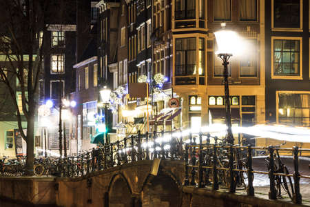 Moody night shot at the canals in the streets of Amsterdam, the Netherlands photo