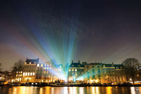 Lightshow over the river Amstel at the canals of Amsterdam, The Netherlands