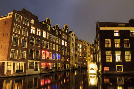 Canal houses at night in the Red Light District in Amsterdam, The Netherlands photo
