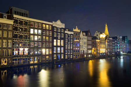 Canal houses at night at the Damrak in Amsterdam, The Netherlands photo