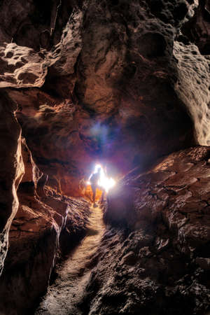 cave exploring: Light shining through the entrance of a beautiful cave in Madagascar, creating a silhouette of a cave exploring tourist  HDR