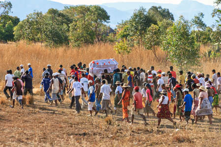 joins: A big crowd joins a local traditional Malagasy funeral procession in Isalo, Madagascar, on September 9, 2013