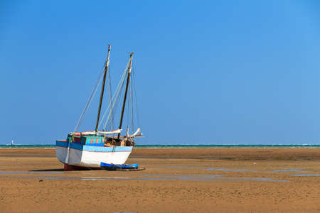 beached: A beached sailing boat at low tide on the beach of Toliara, Madagascar Stock Photo