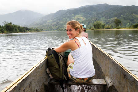 rainforest: Beautiful tourist on a trip in a traditional boat on a river in Masoala national park Madagascar Stock Photo