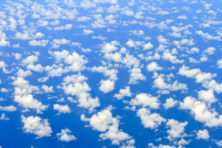 Aerial view on some clouds in the sky above the ocean seen from above