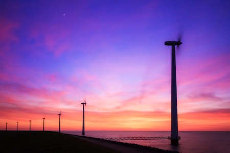 markermeer: Beautiful sunset at the dike with wind turbines at the Markermeer in the Netherlands Stock Photo