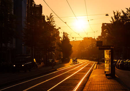 city of sunrise: Beautiful urban sunrise in the city of Amsterdam the Netherlands at the tram stop Stock Photo