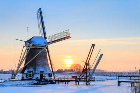 Beautiful dutch windmill near Baambrugge in the Netherlands covered in snow with ice on the river at sunset 스톡 콘텐츠