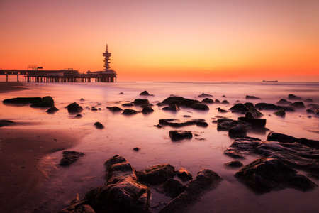 scheveningen: Beautiful sunset at the beach of Scheveningen in the Netherlands with the famous Pier in the background
