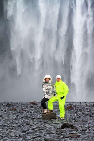 skogafoss waterfall: Two beautiful tourists in front of the mighty Skogafoss waterfall in Iceland
