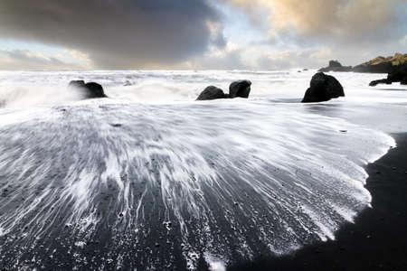 mare agitato: Bel tramonto vista della sabbia nera e mare agitato in spiaggia di Vik in Islanda Archivio Fotografico