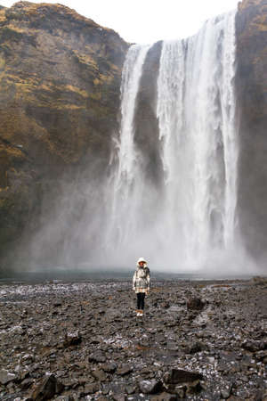 skogafoss waterfall: Beautiful female tourist dwarfed in front of the mighty Skogafoss waterfall in Iceland